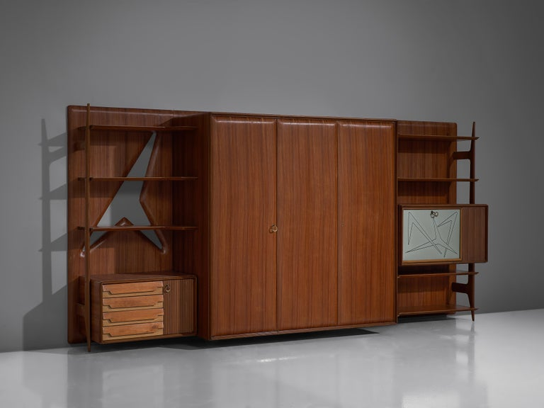 Wall unit, mahogany, lacquered wood, brass,glass, Italy, 1960s.  This Italian wall unit convinces both visual and functional.Itoffers a variety of different storage possibilities. A three door cabinet is placed in the centrum which provides a