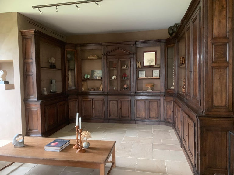 A good late 18th century Italian neoclassical library room panneling. This room consists of one central bookcase with a tympan centerpiece. At both sides angle cabinets with hand blown glass are integrated. They are followed at both angles with an