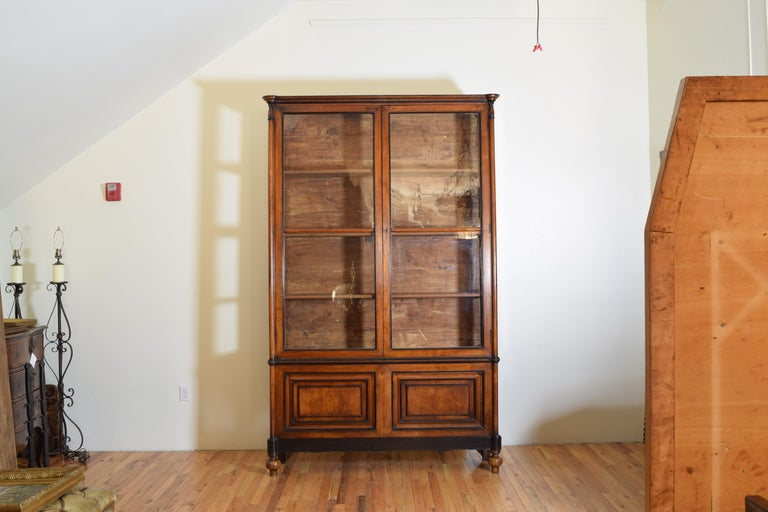 This unique cabinet is both tall and shallow and likely came from a retail shop of some sort, the upper portion has glass doors and glass sides allowing viewing of contents from all angles in the room, the outer sections of the doors are rounded as