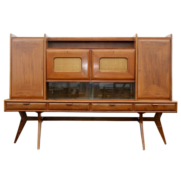 A Mid-Century Modern Italian wall unit in walnut featuring multiple storage and display areas. Four drawers, including two partitioned for flatware. Two drop front, mirrored dry bars. Two doors concealing shelved storage. Multiple display areas.