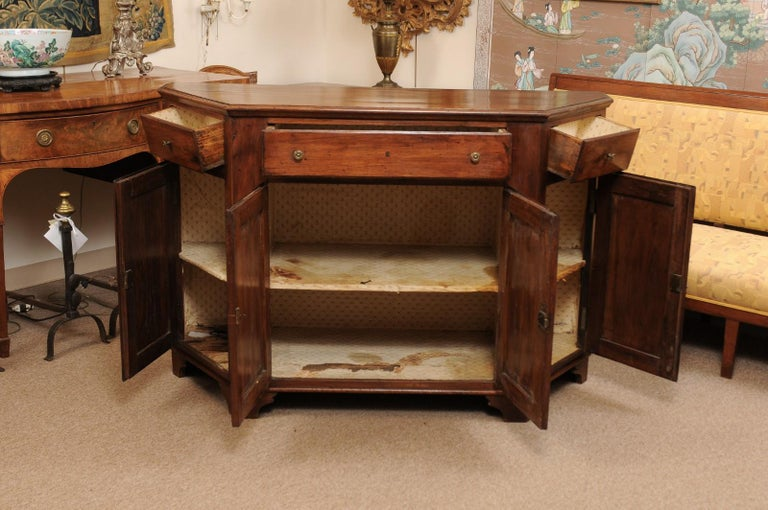 An early 19th Century Italian Walnut Credenza with Canted Sides, 3 drawers & 4 Cabinets below ending in bracket feet.
