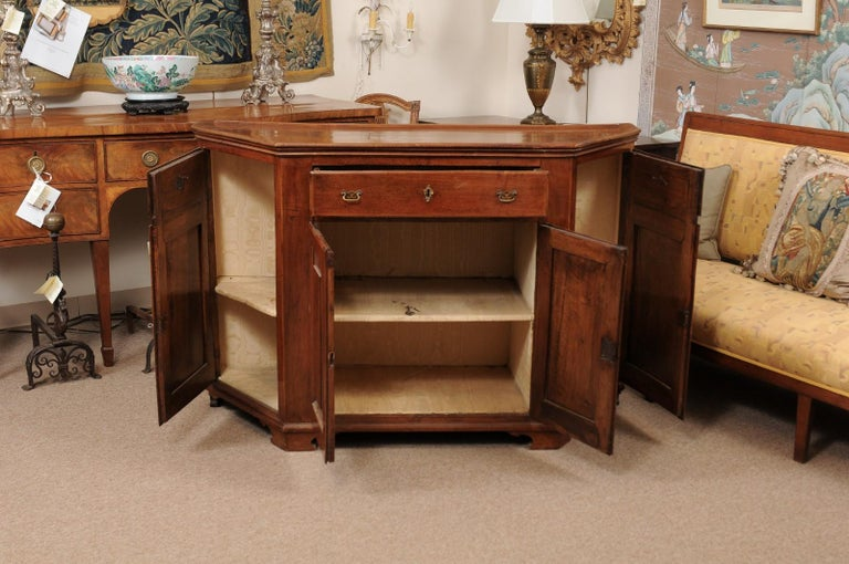Early 19th century Italian walnut credenza with canted sides, 3 drawers with brass hardware and 4 cabinets below with raised paneling ending in carved bracket feet.