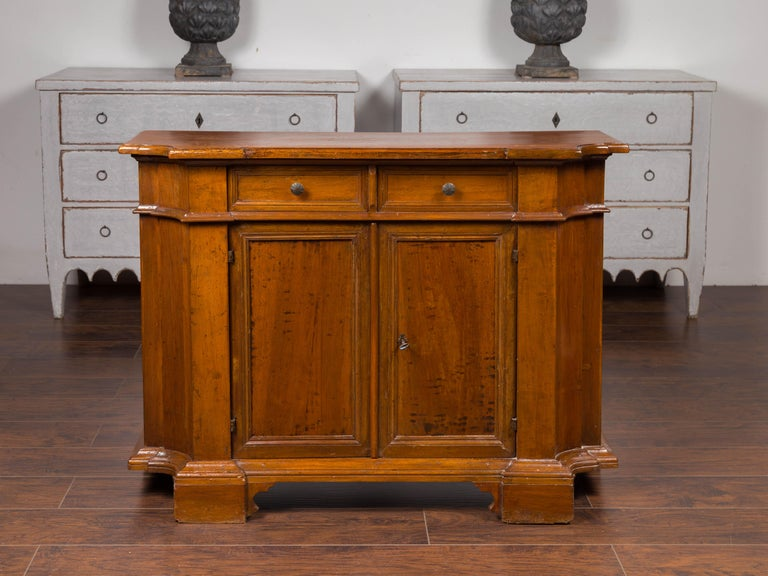 An Italian walnut credenza from the mid-19th century, with two drawers over two doors, bracket feet and curving sides. Born in Italy during the third quarter of the 19th century, this walnut credenza features a single plank top with rounded edges,