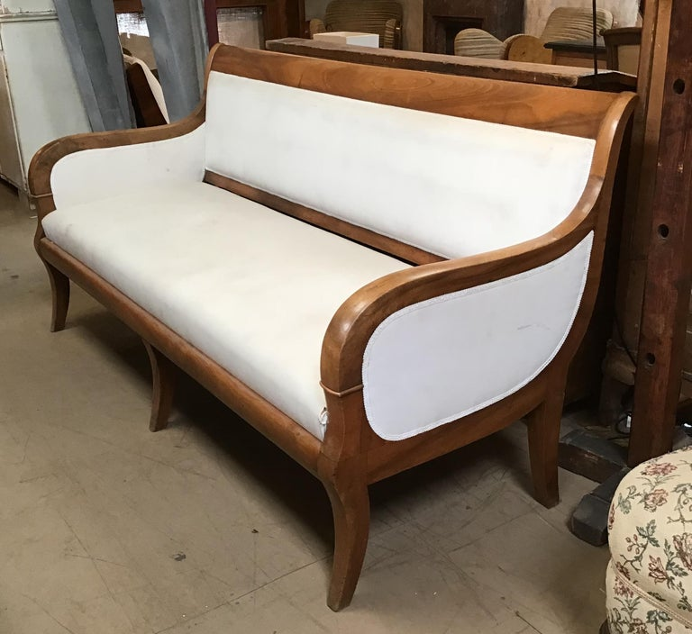 Italian walnut sofa with white upholstery from 1920s. This sofa has already been completely restored.
