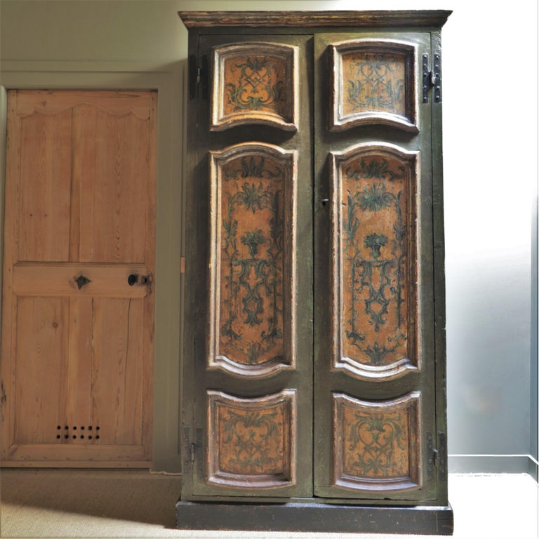 This Italian wardrobe dates from the 18th century. It is adorned with floral and vegetal patterns and painted in shades of green and ochre.