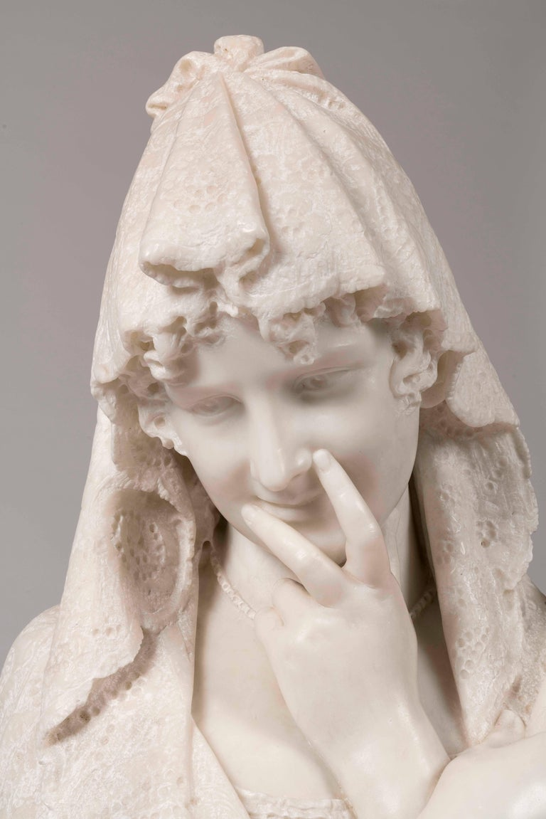 A Carrara marble bust of a shy maiden Signed C Lapini, Firenze  Rising from a circular waisted socle, the maiden holds a fan, and coyly covers her smile with her hand; her lacework mantilla covers her head and shoulders, and is draped over the