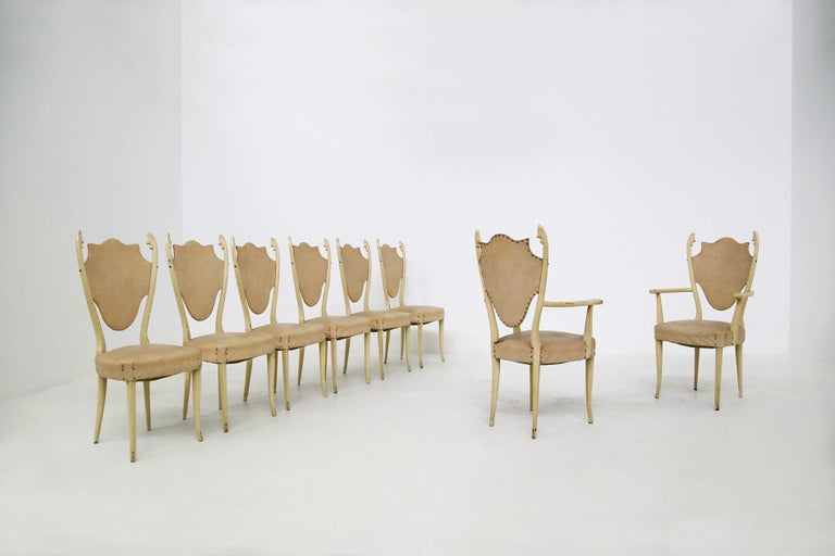 Sculptural Italian chairs of the 1950s, designed by Carlo Enrico Rava. The chairs are in white lacquered ashwood. The set consists of two table heads and four diners. Their eccentricity is its wood carved in the tips of each seat, almost reminiscent