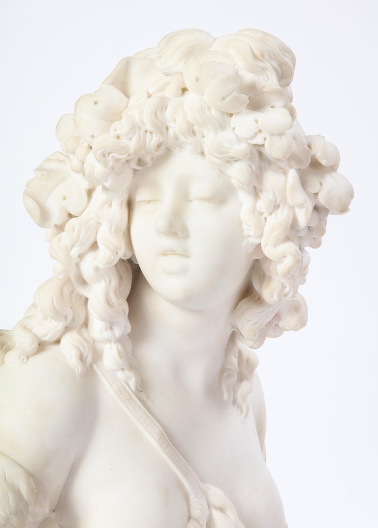 This work is a Baroque-style carved white marble bust of Bacchante with Classical features raised on a decorative turned plinth. The bust was probably carved in Italy during the explosion of decorative sculpture in the 19th and 20th centuries.