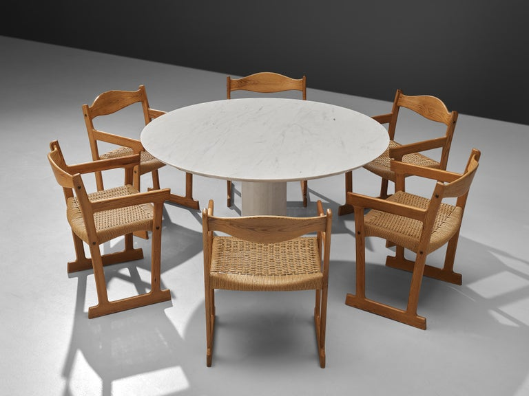 Round dining table, white marble, Italy, 1960s  This wonderful combination of wooden dining chairs around a round marble table forms a striking combination of colors and textures. The pedestal table stands on a cylindric base and a round feet.