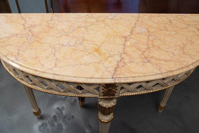This is a decorative Italian Louis XVI style white painted and parcel gilt demilune console, the sepia variegated marble top with molded edge over lattice-form frieze. The demilune console is supported by round tapering fluted legs. 20th century.