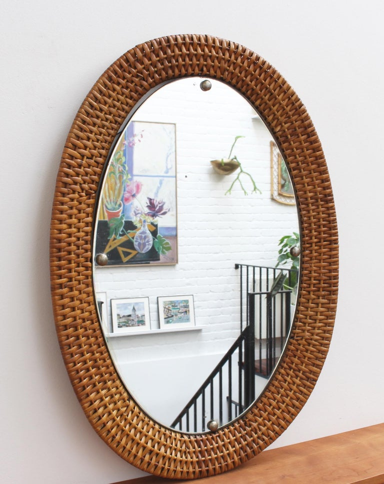 Italian wicker rattan wall mirror (circa 1960s). A distinctive vintage mirror which transports you immediately to another place and another time, perhaps the Italian Riviera or Miami's South Beach circa 1960. Its substantial glass is oval-shaped,