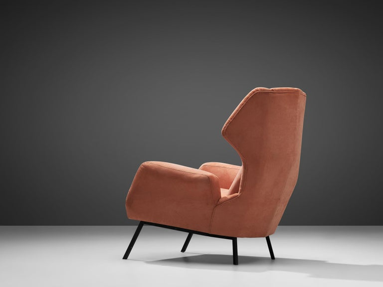 Wingback armchair, salmon colored upholstery, metal legs, Italy, 1960s  This Classic Italian post-war wingback chair has unusually high back and gracious wings that contains dramatized pointed corners. The elegant armrests are slightly curved