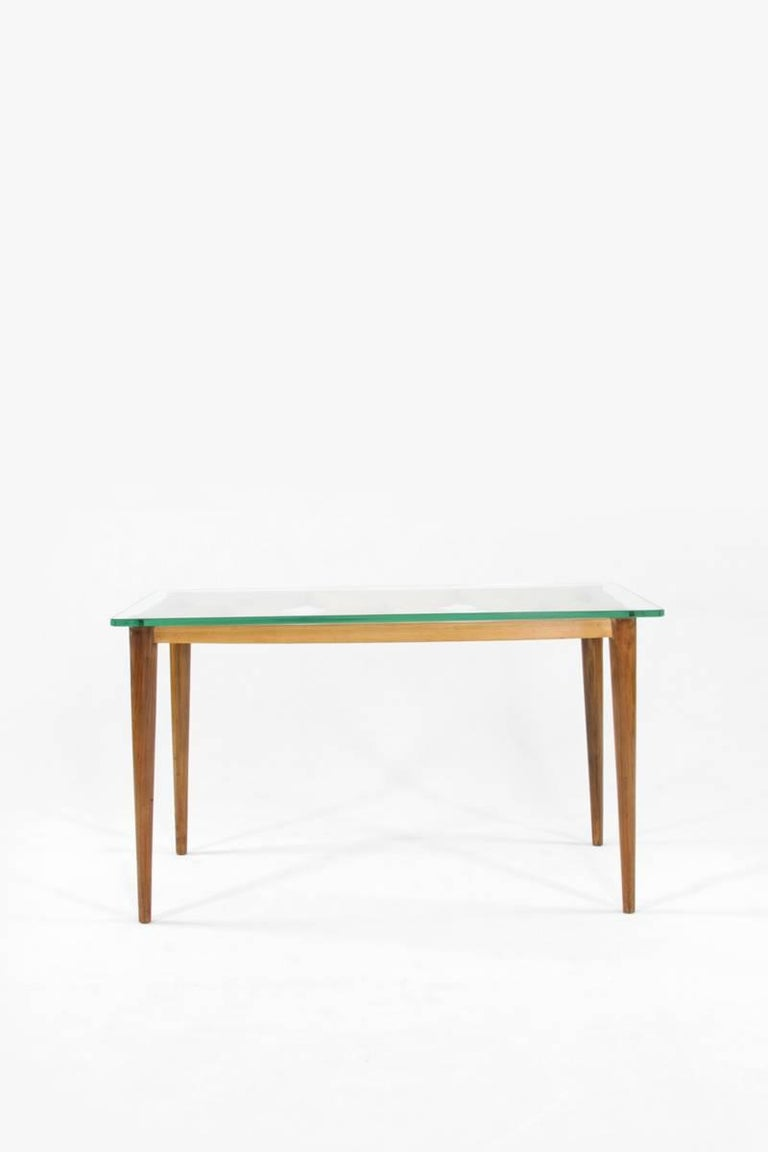 This coffee table in the manner of Paolo Buffa is from the Italian 1950s. It is designed with simplicity but appears elegant with walnut and maple and a crystal glass top.