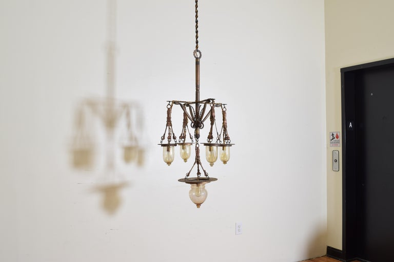Originally an oil lantern and probably from Venice, Italy, with 4 arms connected to the central standard by horizontal brackets and diagonal decorative serpents, each end with a hanging glass globe, the bottom of the chandelier issuing one larger