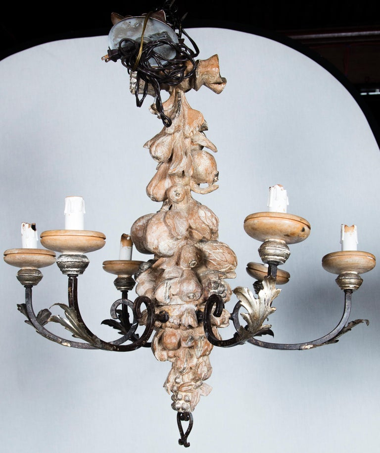 Six-light wrought iron and carved wood Italian chandelier. Deeply and intricately carved, circa 1960s.