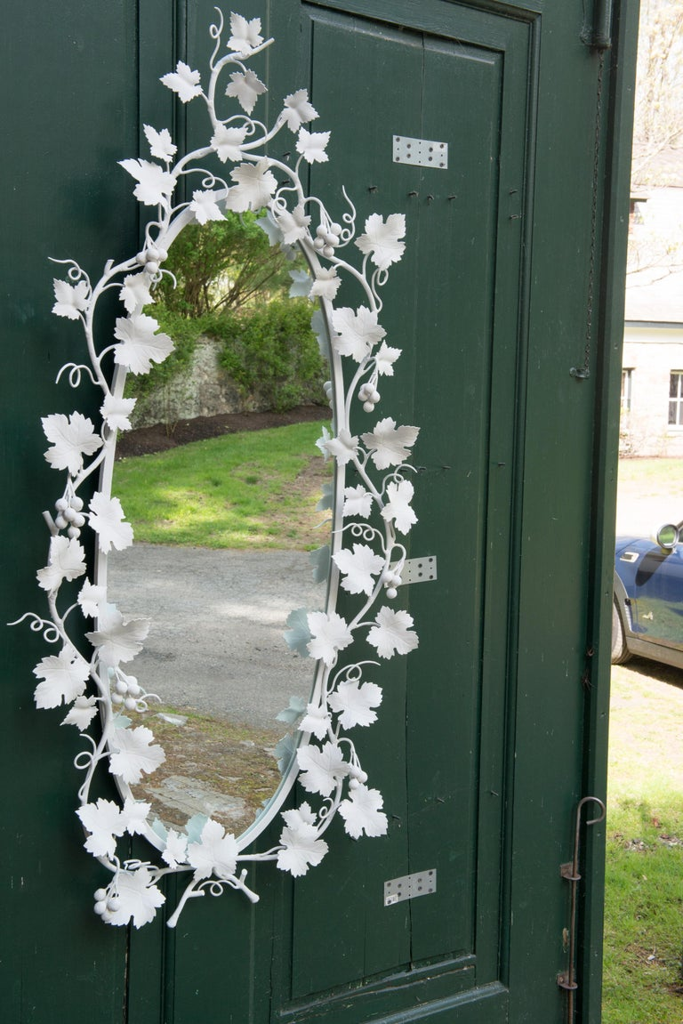 Large oval white painted Italian wrought iron grape and grape vine mirror.