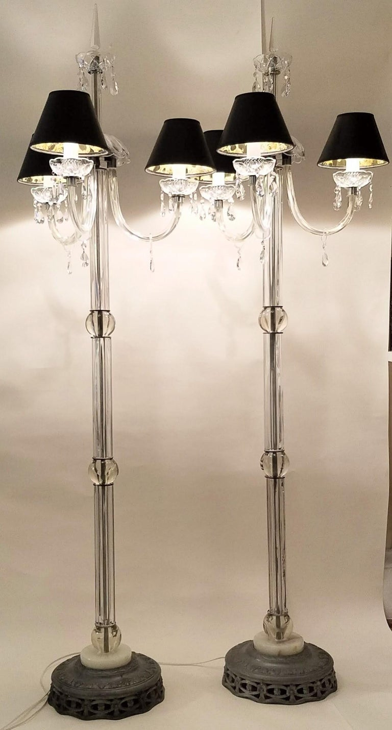 A pair of lead crystal floor lamps each with three chandelier style cast glass arms. Each arm extends 9 inches from the fluted glass central columns and crystal ball.  The fluted glass sections are capped with nickel plated caps and separated by