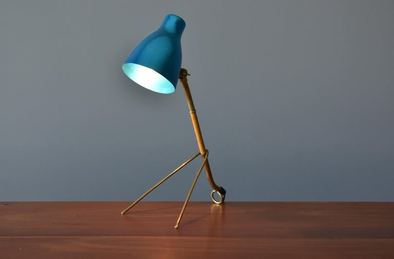 A rare modernist table lamp by Finnish producer Itsu. Base features molded and bent brass wrapped in natural leather. Adjustable screen in anodized aluminum.