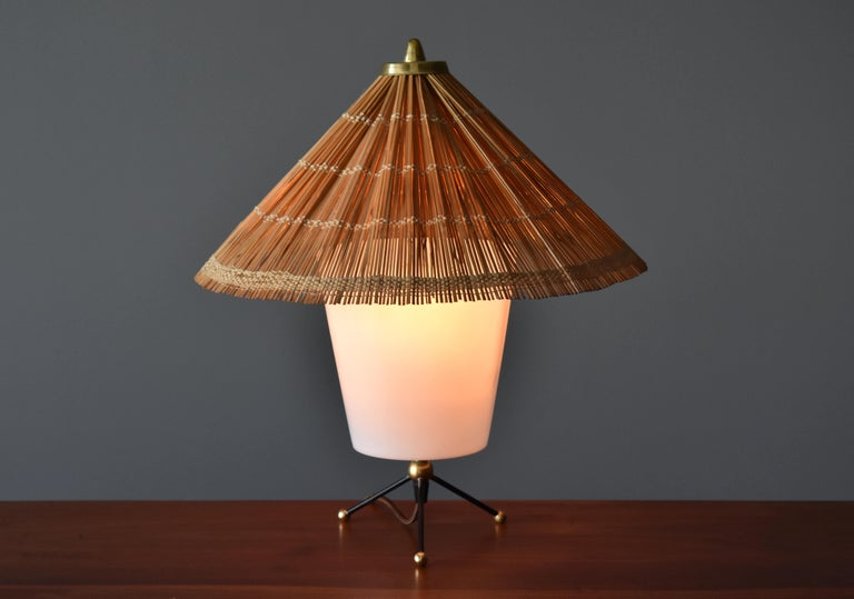 A lamp by Finnish producer Itsu. The base features an interesting mix of Brass, black painted steel and acrylic. Warm and diffused light radiates through the large handmade reed screen. Marked.   Model illustrated in manufacturers