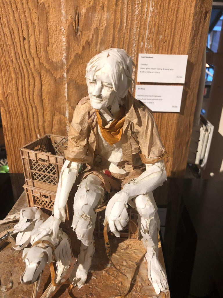 This realistic sculpture is created from scraps of paper and glue.  The sculpture is inspired by the characters found in cities around the world.  In this case, a man and his dog have picked a spot to sit and rest together in a makeshift living room