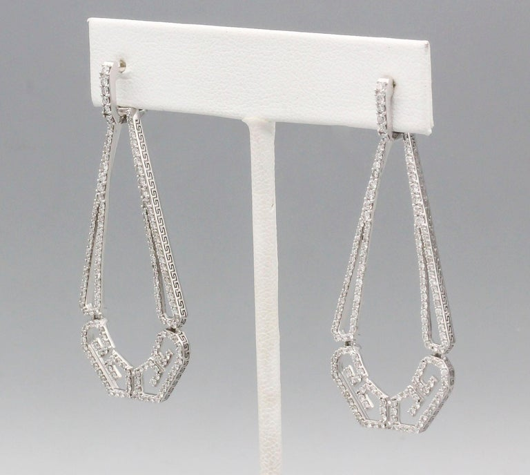 Fine diamond and 18K white gold drop earrings by Ivanka Trump. They feature high grade round cut diamonds throughout, approx. 1.5-2.0cts total weight.  The earrings are further decorated with a Greek key like pattern along its edges. Over 2 inches