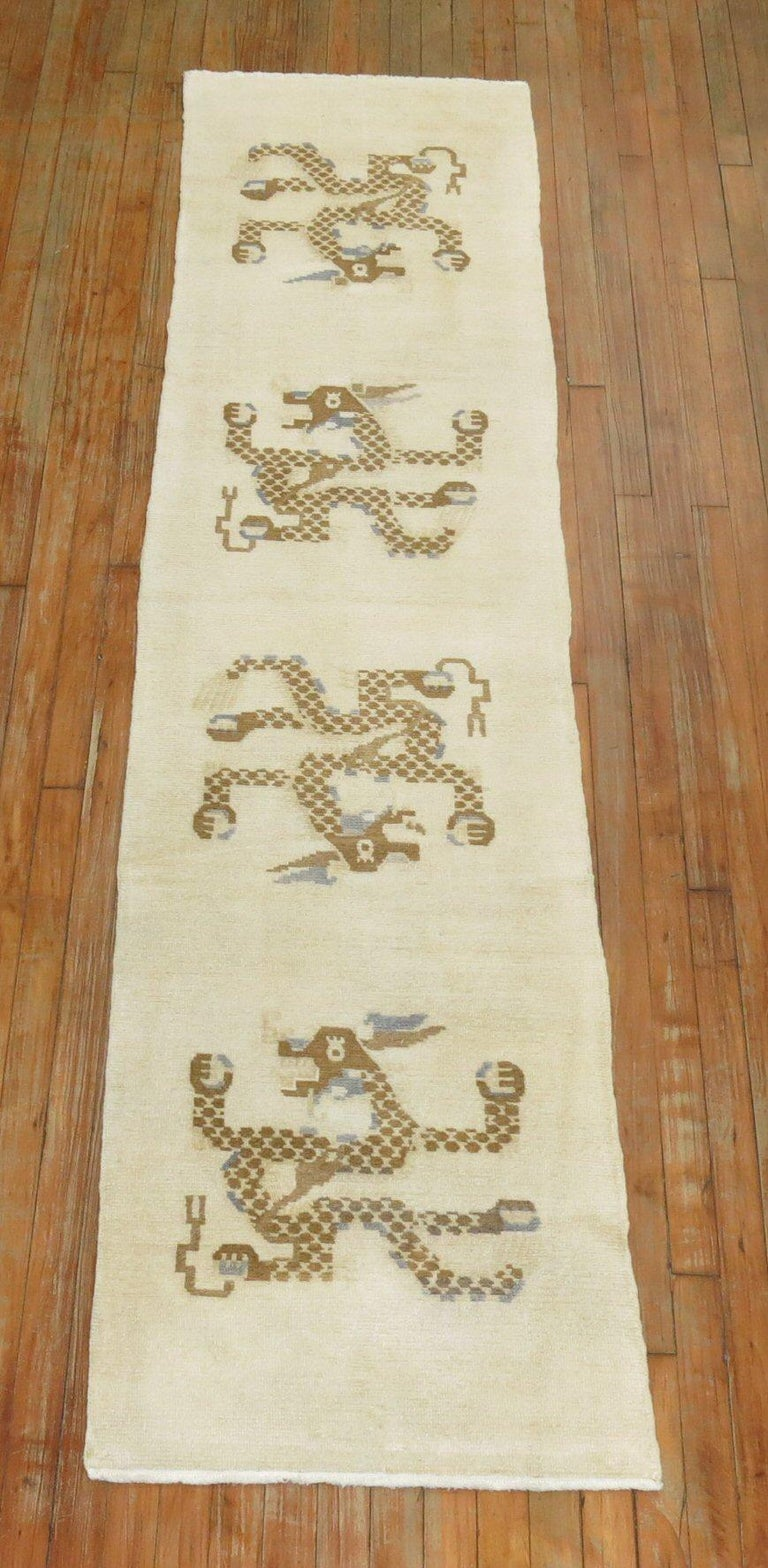 A vintage Tibetan runner from the middle of the 20th century with a 4 brown dragons floating on a white ground.  Measures: 2'1