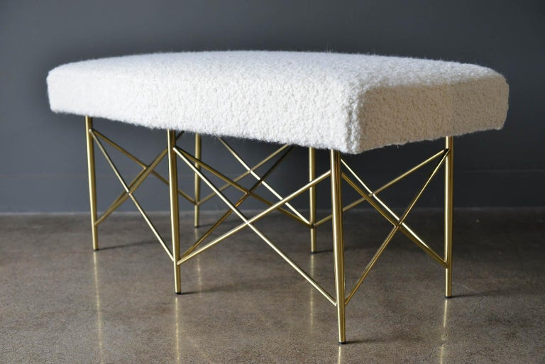 Ivory Bouclé and brass X-base ottoman or bench, circa 1970. Professionally recovered in beautiful soft ivory or cream wool bouclé fabric with new foam. Bench base is brass and has been polished. Beautiful trapezoid shape, could be used at the end of