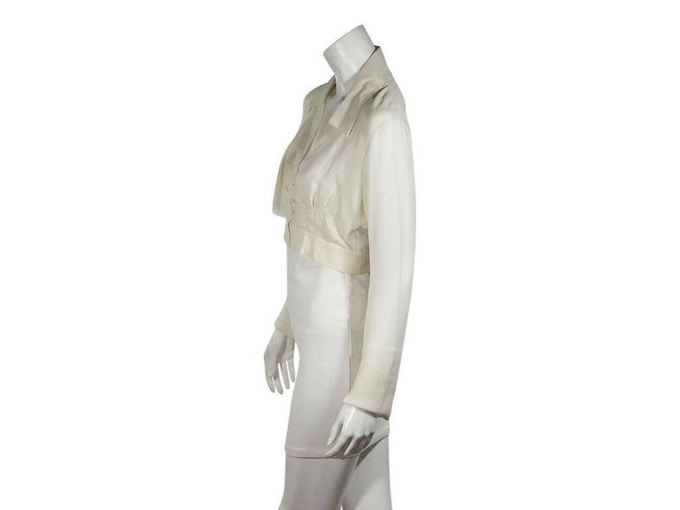 Product details:  Ivory silk cropped blouse by Chanel.  Spread collar.  V-neck.  Long sleeves.  Button-front closure.  Draped-bodice detail.  Banded hem.  Label size FR 38.  34