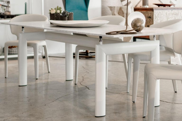 """The base of this LC 6 table from Cassina has four supporting points with steel threaded shanks, permitting height adjustment up to 2"""". The Carrara top with ivory enameled base makes this table a versatile kitchen or dining table.   The base of"""