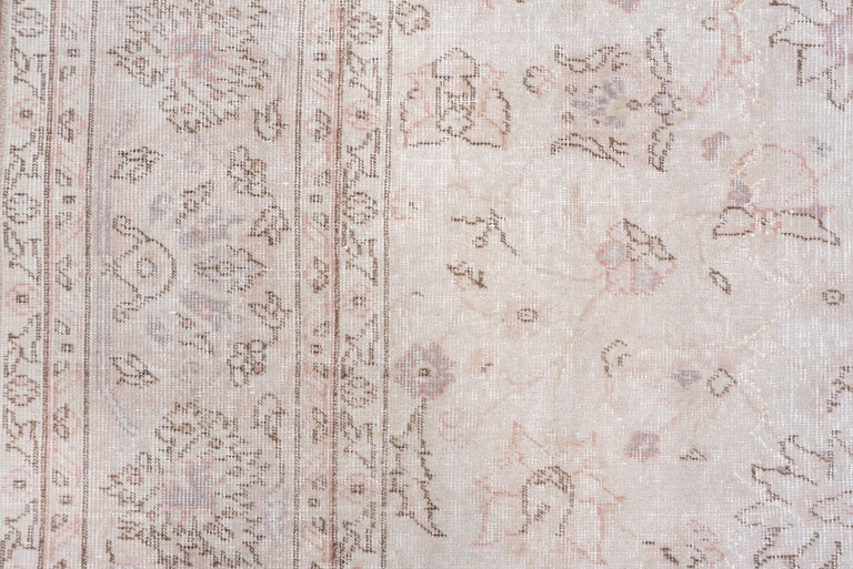 Small lotus palmettes and daisy rosettes, all with delicate cherry brown details, symmetrically swirl about the ecru field, framed by a jagged palmette border.
