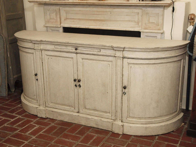 A painted oak four door buffet with curved doors on each end, and pull out shelf in center.