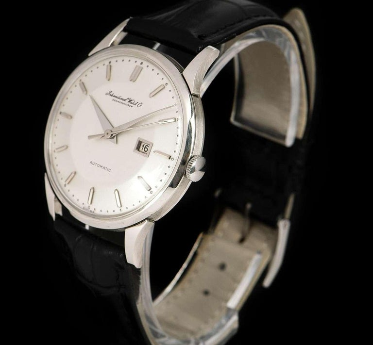 A 34.5 mm Platinum Vintage Men's Dress Wristwatch, silver dial with applied hour markers, date at 3 0'clock, a fixed platinum bezel, a brand new black leather strap (not by IWC) with an original stainless steel pin buckle, plastic glass, automatic