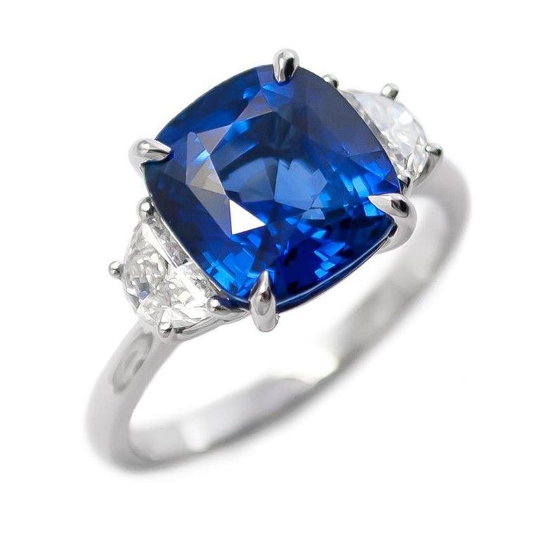 This elegant ring fresh from the J. Birnbach workshop features a vivid and mesmerizing 5.06 ct Sapphire cushion. Set in a handmade, three-stone ring with half moon side stones = 0.55 ctw of G color and VS clarity, this ring is another fantastic