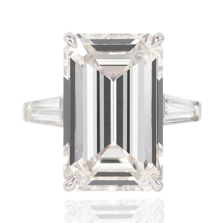 This exquisite J. Birnbach original features a GIA Certified 11.43 ct Emerald cut diamond of H color and VS1 clarity. Flanked by a pair of tapered baguettes = approximately 1.50 ctw set in a platinum mounting, this ring will forever remain a classic