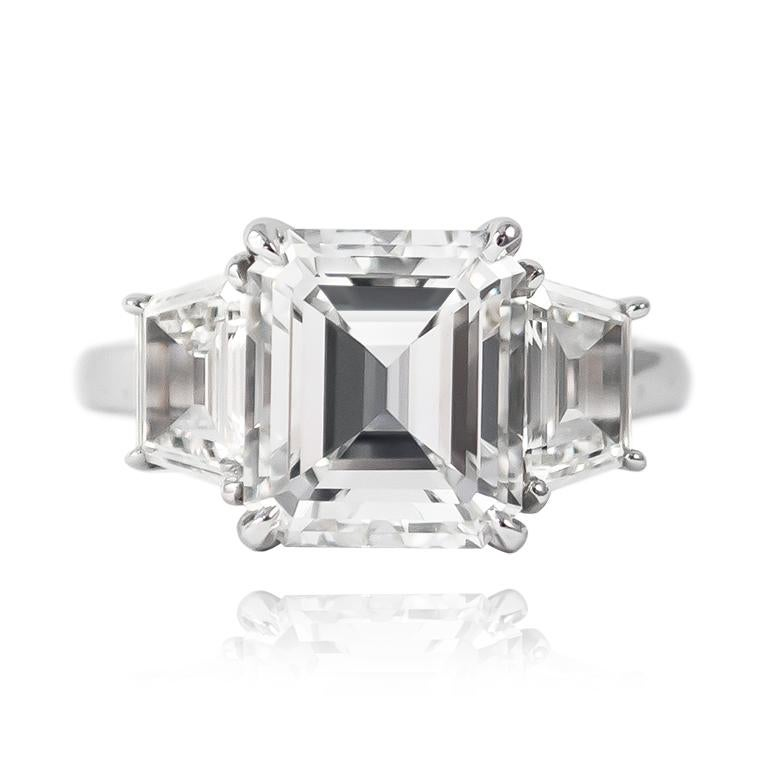 This mesmerizing ring features a 3.04 ct Emerald cut of E color and VS1 clarity. Set in a handmade, platinum setting with step-cut trapezoid side stones = 1.12 ctw, this piece is a breathtaking look that is guaranteed to make them stop and stare!