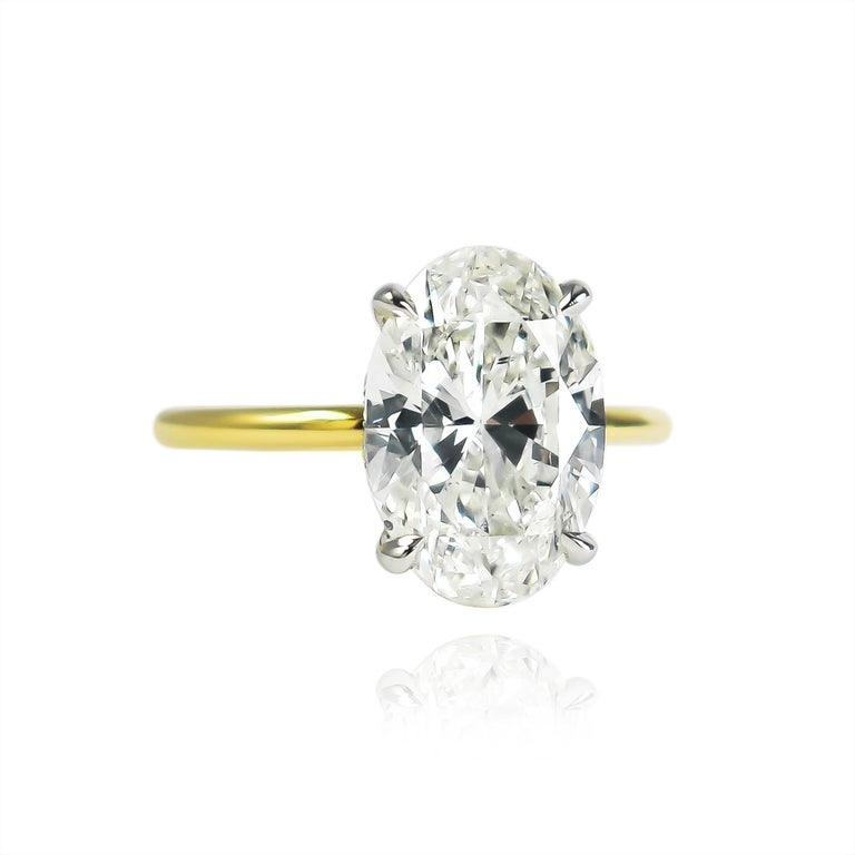 This breathtaking and delicate ring fresh from the J. Birnbach workshop features a GIA certified 3.50 carat oval brilliant cut diamond of J color and SI2 clarity. Set in a handmade, 18K yellow gold and platinum solitaire ring with a hidden halo