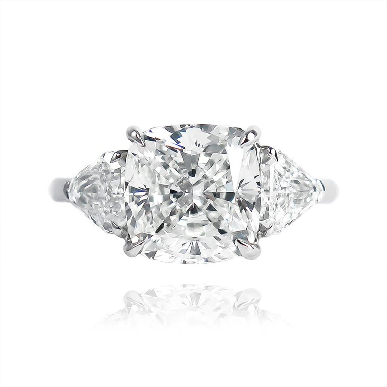 This scintillating ring features a 3.71 carat cushion modified brilliant cut diamond of I color and VS1 clarity... Set in a handmade, platinum, three-stone ring with shield side stones = 0.85 ctw, this piece is contemporary, bold, and beautiful