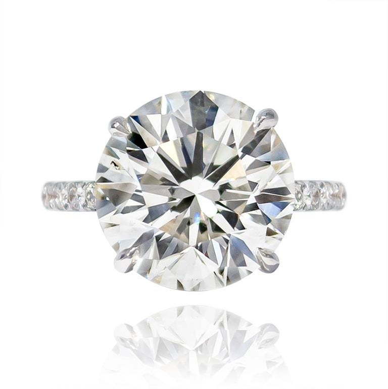This magnificent ring features a 7.02 carat Brilliant Round diamond of J color and SI2 clarity. Lively and scintillating, this diamond ring is an unbelievably large look for the price point. The handmade, platinum mounting is set with 12 diamonds =
