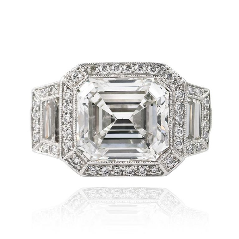 This magnificent, new J. Birnbach acquisition features a 7.34 ct Emerald cut diamond of H color and I1 clarity.. Set in a three-stone ring with step-cut trapezoid side stones = 0.80 ctw and 193 brilliant round diamonds = 3.50 ctw, this ring is a