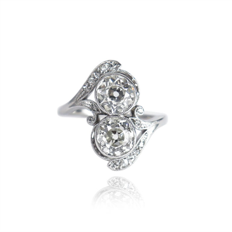 This beautiful and charming bypass ring features features two Old European cut diamonds of I/J color and SI clarity = approximately 2.30 carat total weight. Set in the original, handmade, platinum ring dated to the 1930s, this piece is exquisitely