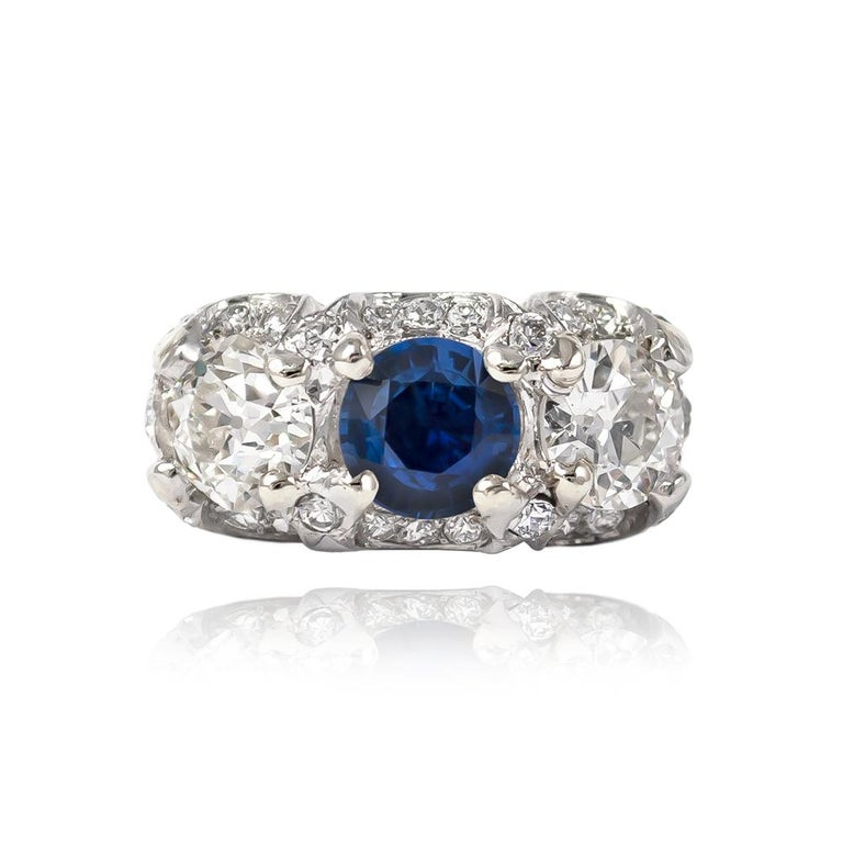 This antique from the J. Birnbach vault features a vibrant, blue sapphire = 1.84 cts & a pair of Old European cut diamond side stones = 2.20 ctw (approximately) of H-I color and SI clarity. Delightfully charming with hand-engraved & scalloped pavé