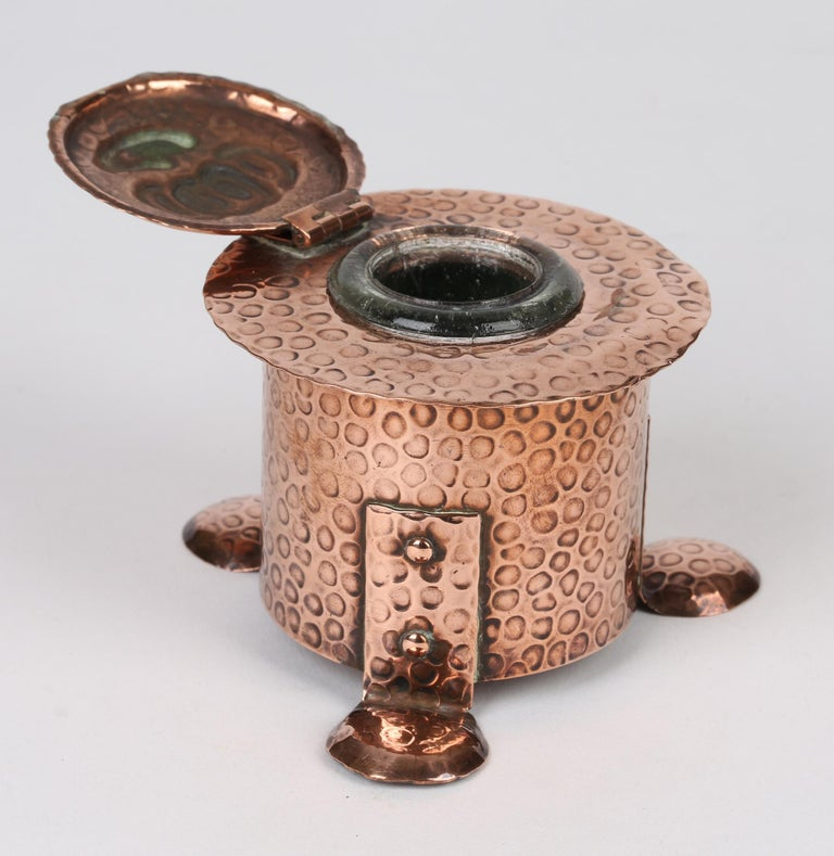 A very stylish Arts & Crafts hand-beaten lidded copper inkwell by J F Poole Hayle dating from around 1895. Made in Cornwall the inkwell is of rounded cylindrical shape and stands raised on three folded flat rounded and domed feet riveted to the