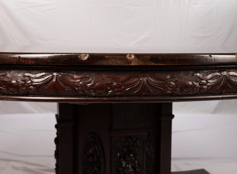 Offering this gorgeous J Horner round dining table. Starting on a stately pedestal bottom that reaches outward to four feet with casters. The body of the pedestal is heavily carved in floral and fruit motifs. The skirts of the table is carved in a