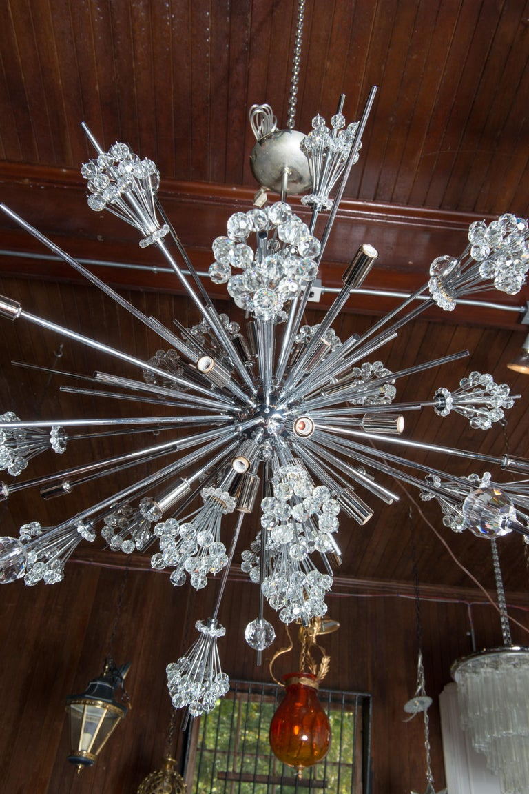 Metropolitan Opera starburst chandeliers were originally made by Hans Harald Rath of the Austrian company, J. & L. Lobmeyr in 1966. This starburst chandelier is made by Lobmeyr in chrome and cut crystal. The chandelier holds 26 bulbs.