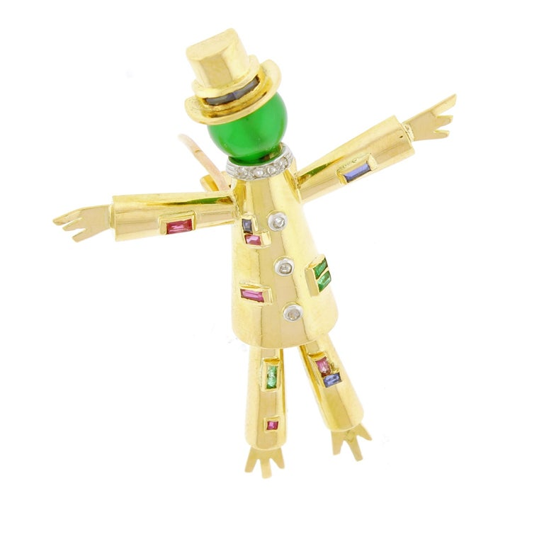 Jacques  Lacloche created the l'épouvantail (scarecrow)  clip brooch to commemorate the opening of his salon in Pairs. The registered design is crafted in 18 karat gold with rubies diamond sapphire emeralds and a green glass bead.  2 inches high