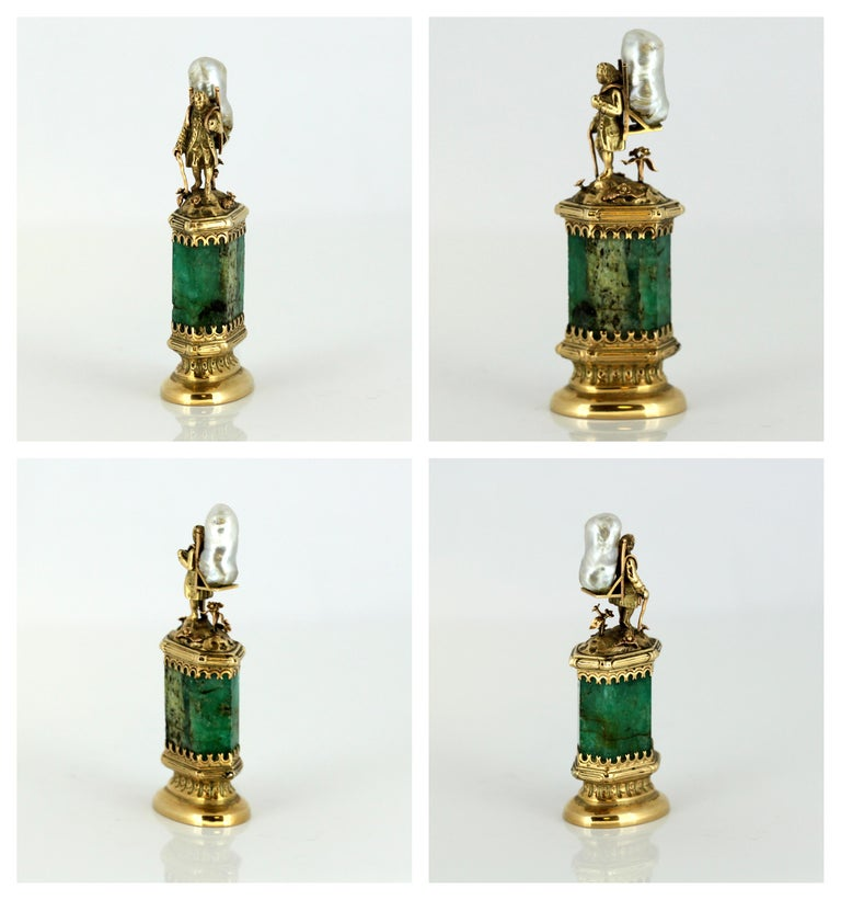 The gold-mounted emerald stem surmounted by a figure in the form of a 18th century marchand ambulant, carrying a large pearl on his back.  Retailed by J. Mandereau / Maison Molgatini, Orléans, circa 1890  Marked in original box - 'Maison Molgatini /
