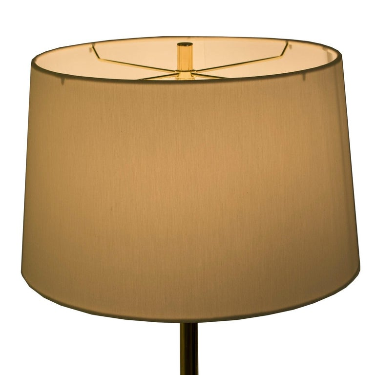Circa 1980's tripod base floor lamp. Sleek design replated with brass base and stem. An elegant example of European Post Modern design. Sourced through from a New York collector.