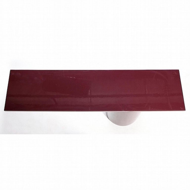 A plum lacquered asymmetric tee cantilevered console table attributed to J. Wade Beam for Brueton, circa 1980s. Cylindrical weighted base flows and interlocks seamlessly with a half cylinder horizontal top. Original finish is high gloss lacquered