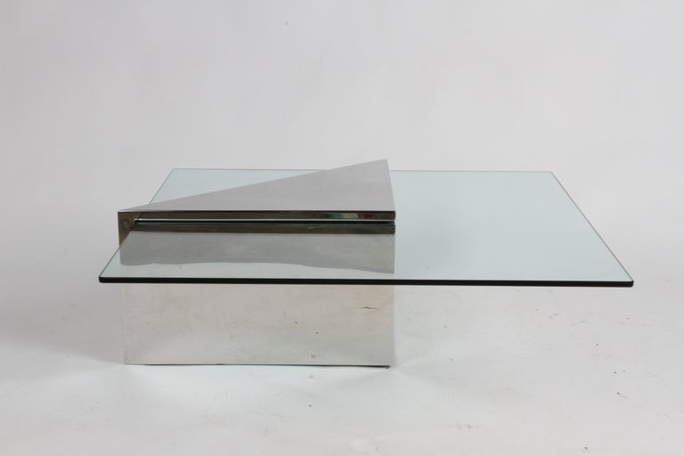 Triform coffee table designed by J. Wade Beam for Brueton, circa 1980s having a polished stainless monolithic triangular base with square glass top. Top of triangular base does show some surface scratches, since its stainless it can be polished out.