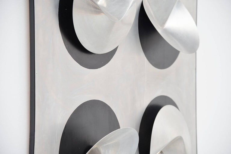 Super nice geometric shaped sculptural artwork designed by Jaap van Hunen (1941), Nijmegen 1970. This very nice large artwork was made of a wooden panel, covered in aluminum and has very nice geometrical shapes in aluminium. It has a black rubber